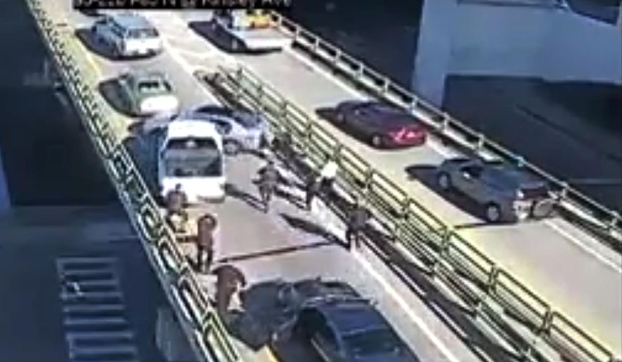 In this Thursday, Nov. 9, 2017 still image from video posted by the Rhode Island Department of Transportation, Providence Police Department officers converge on a truck driven into another vehicle by Joseph Santos on a highway on-ramp in downtown Providence, R.I. Police shot Santos dead, and injured passenger Christine Demers, who was hospitalized. (Rhode Island Department of Transportation via AP)