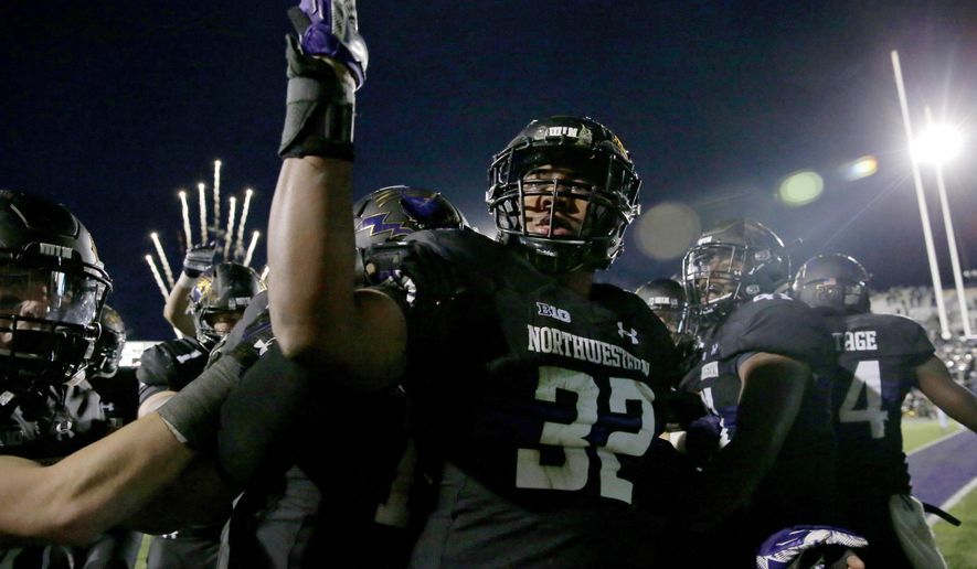 FILE - In this Oct. 28, 2017, file photo, Northwestern linebacker Nate Hall (32) celebrates with teammates after intercepting a pass from Michigan State quarterback Brian Lewerke during the third overtime of an NCAA college football game in Evanston, Ill. Northwestern, which has won three consecutive overtime games, plays Purdue this week. (AP Photo/Nam Y. Huh, File)