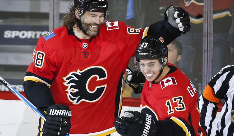 Calgary Flames' Jaromir Jagr, left, of the Czech Republic, celebrates his first goal with the team, with Johnny Gaudreau during the second period  against the Detroit Red Wings in an NHL hockey game Thursday, Nov. 9, 2017, in Calgary, Alberta. (Jeff McIntosh/The Canadian Press via AP)