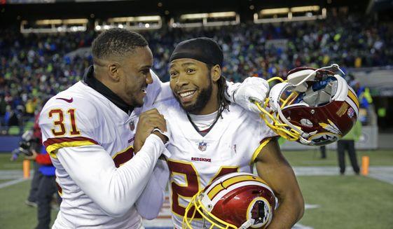 Washington Redskins cornerbacks Josh Norman, right, and Fabian Moreau, left, celebrate after an NFL football game against the Seattle Seahawks, Sunday, Nov. 5, 2017, in Seattle. Washington won 17-14. (AP Photo/Stephen Brashear)