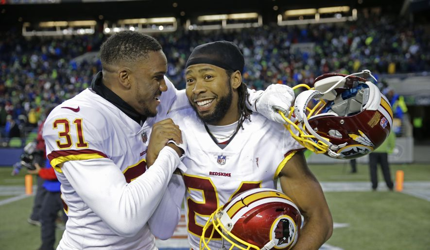 Washington Redskins cornerbacks Josh Norman, right, and Fabian Moreau, left, celebrate after an NFL football game against the Seattle Seahawks, Sunday, Nov. 5, 2017, in Seattle. Washington won 17-14. (AP Photo/Stephen Brashear)
