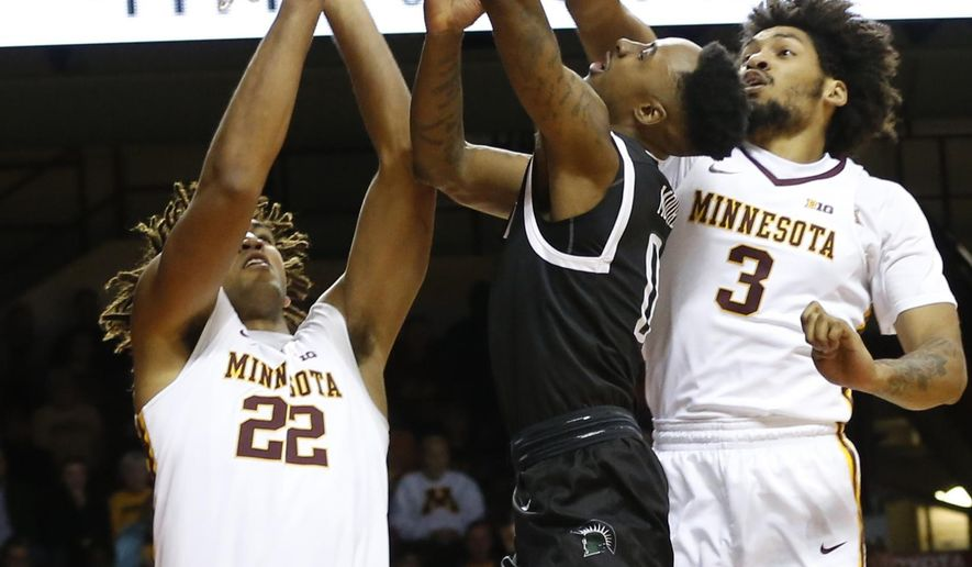 South Carolina Upstate's Malik Moore, center, lays up as Minnesota's Reggie Lynch, left, and Jordan Murphy defend during the first half of an NCAA college basketball game Friday, Nov. 10, 2017 in Minneapolis. (AP Photo/Jim Mone)
