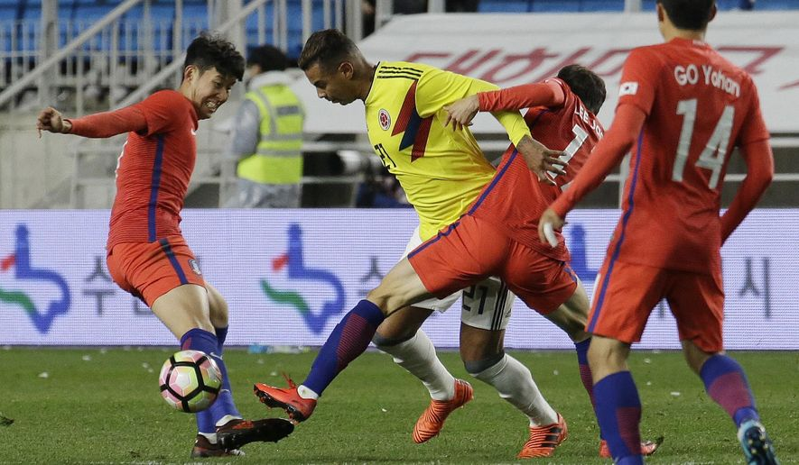 Colombia's Edwin Cardona, second from left, fights for the ball against South Korea' Lee Jae-sung and Son Heung-min, left, during their friendly soccer match at Suwon World Cup Stadium in Suwon, South Korea, Friday, Nov. 10, 2017. (AP Photo/Ahn Young-joon)