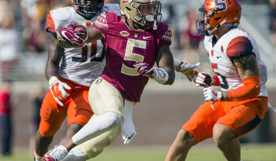 Florida State wide receiver Ermon Lane cuts between Syracuse linebacker Parris Bennett, left, and defensive back Rodney Williams in the second half of an NCAA college football game in Tallahassee, Fla., Saturday, Nov. 4, 2017. Florida State defeated Syracuse 27-24. (AP Photo/Mark Wallheiser) (AP Photo/Mark Wallheiser)
