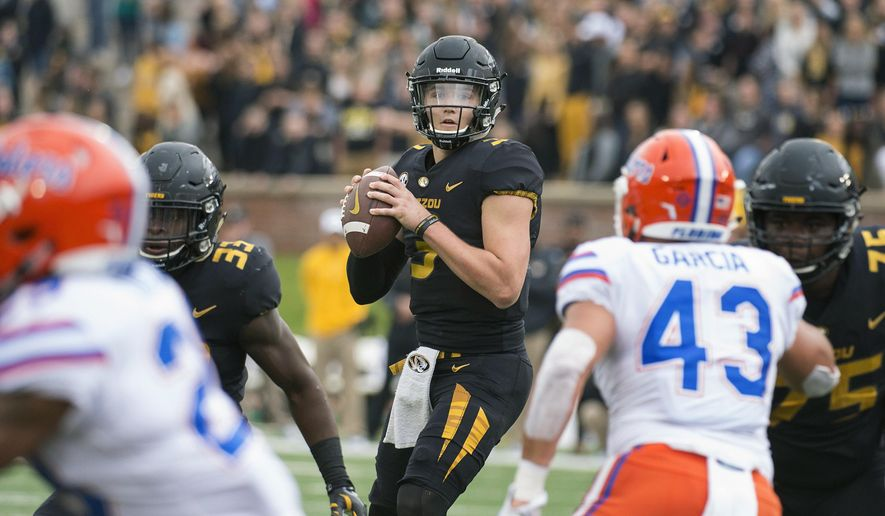 FILE - In this Nov. 4, 2017, file photo, Missouri quarterback Drew Lock looks for an open receiver between Florida defenders during the first half of an NCAA college football game in Columbia, Mo. Missouri (4-5, 1-4) is building off of a 45-16 trouncing of Florida last weekend. Lock threw for 228 yards, three touchdowns and an interception on 15-for-20 passing in the win, and the Tigers rushed for 227 yards. Missouri plays Tennessee this week. (AP Photo/L.G. Patterson, File)