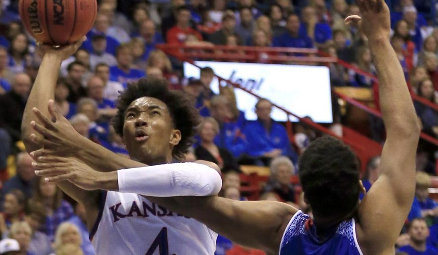 Kansas guard Devonte' Graham, left, is fouled by Tennessee State forward Ken'Darrius Hamilton during the first half of an NCAA college basketball game in Lawrence, Kan., Friday, Nov. 10, 2017. (AP Photo/Orlin Wagner)