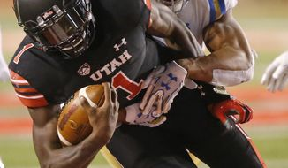 UCLA linebacker Kenny Young, rear, tackles Utah quarterback Tyler Huntley (1) during the second half of an NCAA college football game Friday, Nov. 3, 2017, in Salt Lake City. (AP Photo/Rick Bowmer)