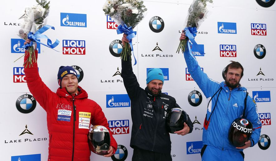 First place Martins Dukurs, of Latvia, center, poses with second-placed Sungbin Yun of South Korea, left, and third-placed Alexander Tretiakov, of Russia, at a World Cup skeleton event in Lake Placid, N.Y., Friday, Nov. 10, 2017. (AP Photo/Peter Morgan)
