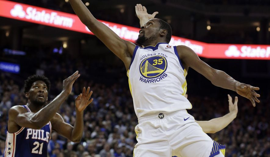 Golden State Warriors' Kevin Durant (35) lays up a shot over Philadelphia 76ers' Joel Embiid (21) during the first half of an NBA basketball game Saturday, Nov. 11, 2017, in Oakland, Calif. (AP Photo/Ben Margot)
