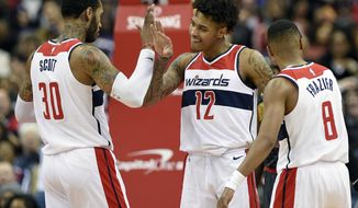 Washington Wizards forward Kelly Oubre Jr. (12) reacts with forward Mike Scott (30) and guard Tim Frazier (8) during the second half of an NBA basketball game against the Atlanta Hawks, Saturday, Nov. 11, 2017, in Washington. The Wizards won 113-94. (AP Photo/Nick Wass)