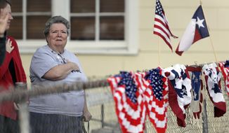 Donna King stands for the national anthem during a Veterans Day event, Saturday, Nov. 11, 2017, in Sutherland Springs, Texas. The event was held in the community, just a block away from the Sutherland Springs First Baptist Church where a man opened killing more than two dozen. Veteran Robert Corrigan, who was killed in the church, was honored during the service. (AP Photo/Eric Gay)