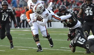Virginia running back Chris Sharp (31) dives for the end zone over the defense of Louisville defensive tackle G.G. Robinson (94) and cornerback Trumaine Washington (15) during the first half of an NCAA college football game, Saturday, Nov. 11, 2017, in Louisville, Ky. (AP Photo/Timothy D. Easley)