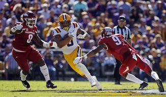 LSU running back Derrius Guice (5)carries between Arkansas linebacker De'Jon Harris (8) and defensive back Santos Ramirez (9) in the first half of an NCAA college football game in Baton Rouge, La., Saturday, Nov. 11, 2017. (AP Photo/Gerald Herbert)