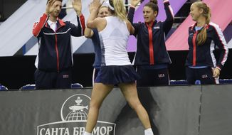 CoCo Vandeweghe of the United States celebrates her victory with teammates during the Fed Cup final match against Aliaksandra Sasnovich of Belarus in Minsk, Belarus, Saturday, Nov. 11, 2017. (AP Photo/Sergei Grits)