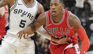 Chicago Bulls guard Kris Dunn, right, drives against San Antonio Spurs guard Dejounte Murray during the first half of an NBA basketball game, Saturday, Nov. 11, 2017, in San Antonio. (AP Photo/Darren Abate)