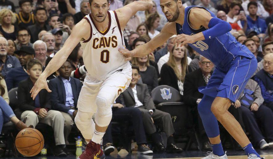 Cleveland Cavaliers forward Kevin Love (0) drives past Dallas Mavericks center Salah Mejri (50) during the first half of an NBA basketball game in Dallas, Saturday, Nov. 11, 2017. (AP Photo/LM Otero)