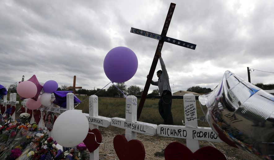 Miguel Zamora stands a cross for the victims of the Sutherland Springs First Baptist Church shooting at a makeshift memorial, Saturday, Nov. 11, 2017, in Sutherland Springs, Texas. A man opened fire inside the church in the small South Texas community on Sunday, killing more than two dozen. Zamora carried the cross for three days to reach the site. (AP Photo/Eric Gay)
