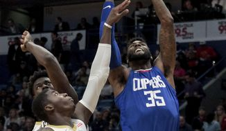 Los Angeles Clippers center Willie Reed (35) shoots over New Orleans Pelicans forward Cheick Diallo (13) and guard Jrue Holiday (11) in the first half of an NBA basketball game in New Orleans, Saturday, Nov. 11, 2017. (AP Photo/Scott Threlkeld)
