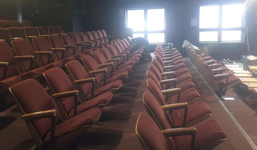 In this Monday, Oct. 30, 2017 photo, Martin Buser unfastens theater seats in the theater at the Alaska Fine Arts Academy in Eagle River, Alaska. The seats were being removed as the theater vacated the space, which had been its home for 11 years. A board member said the arts academy is in the process of looking for a new permanent home. (Matt Tunseth/Chugiak-Eagle River Star via AP)