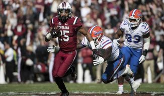 South Carolina running back A.J. Turner (25) runs away from Florida linebacker Vosean Joseph (11) and David Reese (33) during the first half of an NCAA college football game Saturday, Nov. 11, 2017, in Columbia, S.C. (AP Photo/Sean Rayford)