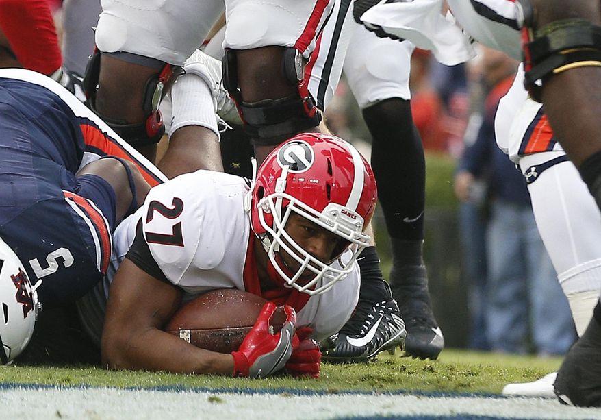 Georgia running back Nick Chubb (27) scores a touchdown against Auburn during the first half of an NCAA college football game on Saturday, Nov. 11, 2017, in Auburn, Ala. (AP Photo/Brynn Anderson)