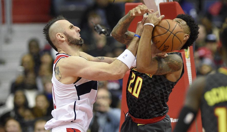 Washington Wizards center Marcin Gortat, left, of Poland, battles for the ball against Atlanta Hawks forward John Collins (20) during the first half of an NBA basketball game, Saturday, Nov. 11, 2017, in Washington. (AP Photo/Nick Wass)