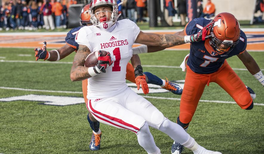 Indiana wide receiver Simmie Cobbs Jr. (1) spins to avoid a tackle by Illinois defensive backs Jaylen Dunlap (1) and Stanley Green (7) during the second quarter of an NCAA college football game Saturday, Nov. 11, 2017, at Memorial Stadium in Champaign, Ill. (AP Photo/Bradley Leeb)