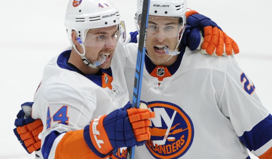 New York Islanders' Calvin de Haan (44) congratulates Anders Lee (27) after his goal against the St. Louis Blues during the third period of an NHL hockey game, Saturday, Nov. 11, 2017, in St. Louis. (AP Photo/Bill Boyce)