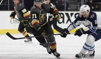 Vegas Golden Knights center William Karlsson (71) battles for the puck with Winnipeg Jets defenseman Jacob Trouba (8) during the second period of an NHL hockey game Friday, Nov. 10, 2017, in Las Vegas. (AP Photo/John Locher)