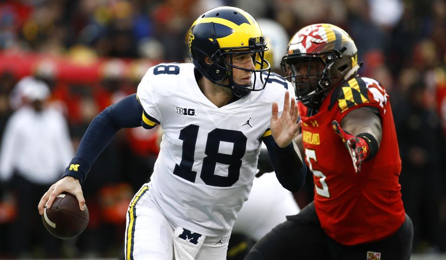 Michigan quarterback Brandon Peters (18) looks for a receiver as he is pressured by Maryland defensive lineman Cavon Walker in the first half of an NCAA college football game in College Park, Md., Saturday, Nov. 11, 2017. (AP Photo/Patrick Semansky)