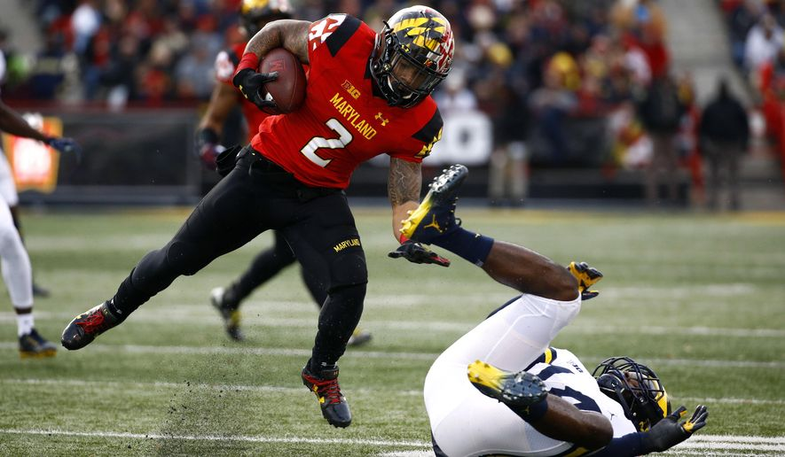 Maryland running back Lorenzo Harrison III, left, spins past Michigan defensive back Josh Metellus as he rushes the ball in the first half of an NCAA college football game in College Park, Md., Saturday, Nov. 11, 2017. (AP Photo/Patrick Semansky) ** FILE **