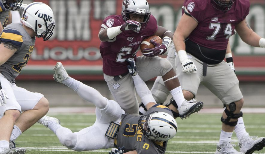 Montana running back Aligah Lee (24) breaks a tackle as he steps over Northern Colorado safety Stone Kane (3) in the first quarter of an NCAA college football game, Saturday, Nov. 11, 2017, in Missoula, Mont. (AP Photo/Patrick Record)
