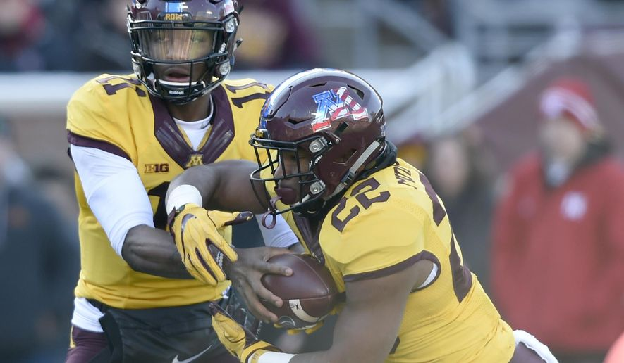 Minnesota quarterback Demry Croft (11) hands the ball to running back Kobe McCrary (22) against Nebraska during the first quarter of an NCAA college football game on Saturday, Nov. 11, 2017, in Minneapolis. (AP Photo/Hannah Foslien)