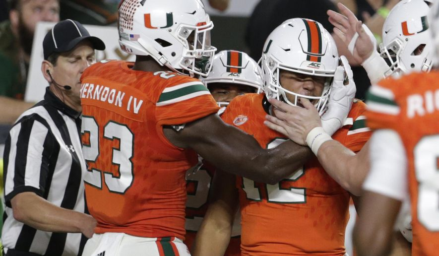 Miami quarterback Malik Rosier (12) is congratulated by Christopher Herndon IV (23) after running for a touchdown during the first half of an NCAA college football game against Notre Dame, Saturday, Nov. 11, 2017, in Miami Gardens, Fla. (AP Photo/Lynne Sladky)