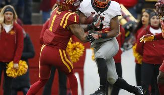 Oklahoma State running back Justice Hill is tackled by Iowa State defensive back D'Andre Payne (1) during a 52-yard run in the first half of an NCAA college football game, Saturday, Nov. 11, 2017, in Ames, Iowa. (AP Photo/Charlie Neibergall)