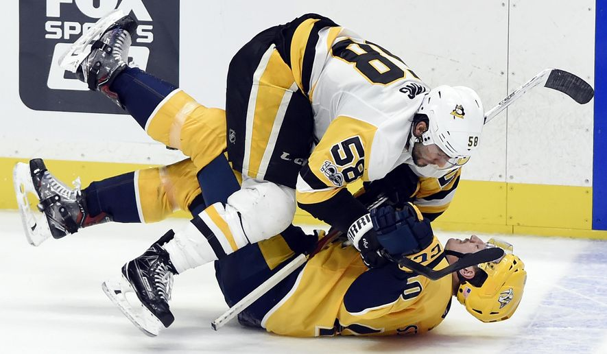 Pittsburgh Penguins defenseman Kris Letang (58) collides with Nashville Predators right wing Miikka Salomaki (20), of Finland, in overtime at an NHL hockey game Saturday, Nov. 11, 2017, in Nashville, Tenn. (AP Photo/Mark Zaleski)