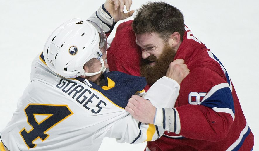 Buffalo Sabres' Josh Gorges, left, and Montreal Canadiens' Jordie Benn, right, fight during first period NHL hockey action in Montreal, Saturday, Nov. 11, 2017. (Graham Hughes/The Canadian Press via AP)
