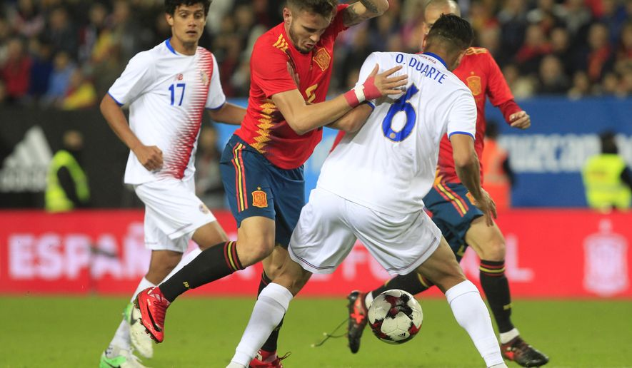 Spain's Saul Niguez, left, controls the ball past Costa Rica's Oscar Duarte during a international friendly soccer match between Spain and Costa Rica in Malaga, Spain, Saturday, Nov. 11, 2017. (AP Photo/Miguel Morenatti)
