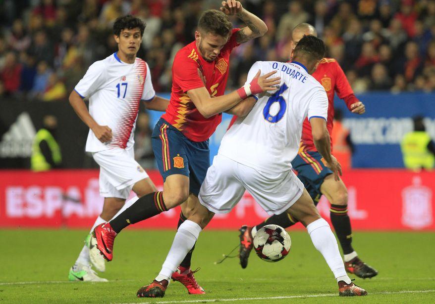 Spain's Saul Niguez, left, controls the ball past Costa Rica's Oscar Duarte during a international friendly soccer match between Spain and Costa Rica in Malaga, Spain, Saturday, Nov. 11, 2017. (AP Photo/Miguel Morenatti)