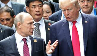 U.S. President Donald Trump, right, and Russia's President Vladimir Putin talk during the family photo session at the APEC Summit in Danang, Saturday, Nov. 11, 2017. (Mikhail Klimentyev, Sputnik, Kremlin Pool Photo via AP)