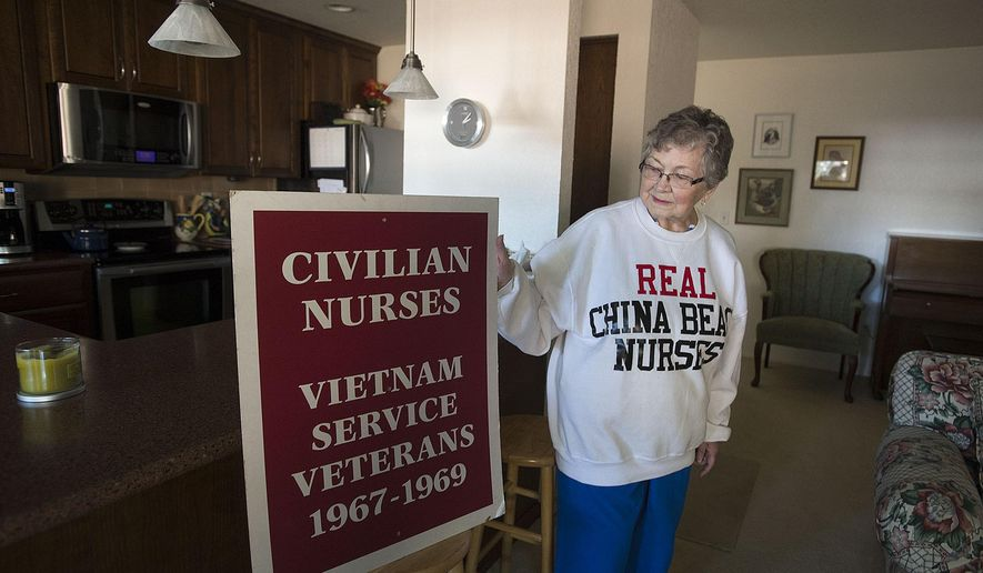 Vietnam War nurse Marion Mullin poses at her Vancouver home on Thursday, Sept. 28, 2017, with the sweatshirt and the sign she carried during the 1993 dedication of the Women's Vietnam War Memorial in Washington D.C. Mullin was a civilian nurse in Danang during the Tet offensive. (Amanda Cowan/The Columbian via AP)