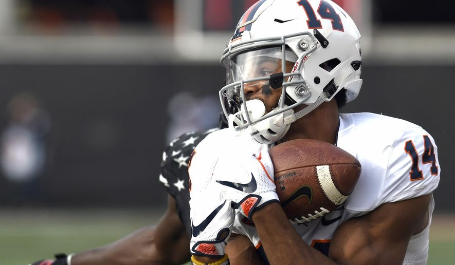 Virginia wide receiver Andre Levrone (14) pulls in a pass ahead of the defense of Louisville cornerback Trumaine Washington (15) during the first half of an NCAA college football game, Saturday, Nov. 11, 2017, in Louisville, Ky. (AP Photo/Timothy D. Easley)