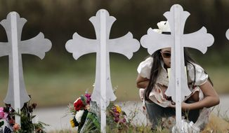 Meredith Cooper visits a makeshift memorial following a worship service for the victims of the shooting at Sutherland Springs Baptist Church, Sunday, Nov. 12, 2017, in Sutherland Springs, Texas. A man opened fire inside the church in the small South Texas community last week, killing more than two dozen. (AP Photo/Eric Gay)