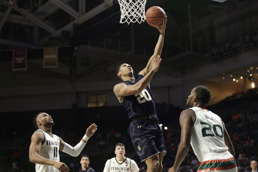 Navy's Isaiah Burnett (11) goes to the basket over Miami's Bruce Brown Jr. (11) and Dewan Huell during the second half of an NCAA college basketball game, Sunday, Nov. 12, 2017, in Coral Gables, Fla. Miami won 89-55. (AP Photo/Lynne Sladky)