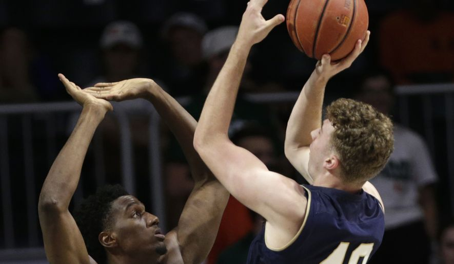 Navy's Evan Wieck (40) shoots as Miami 's Ebuka Izundu (15) defends during the first half of an NCAA college basketball game, Sunday, Nov. 12, 2017, in Coral Gables, Fla. (AP Photo/Lynne Sladky) **FILE**
