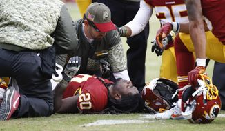 Trainers tend to Washington Redskins running back Rob Kelley (20) after an injury during the first half of an NFL football game against the Minnesota Vikings in Landover, Md., Sunday, Nov. 12, 2017. (AP Photo/Patrick Semansky)