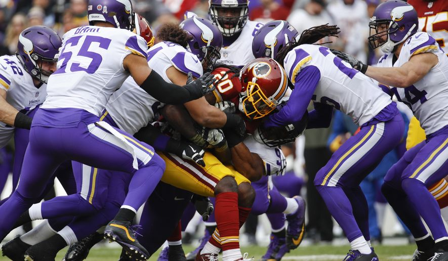 Washington Redskins running back Rob Kelley (20) is swarmed by the Minnesota Vikings defense during the first half of an NFL football game in Landover, Md., Sunday, Nov. 12, 2017. (AP Photo/Patrick Semansky)