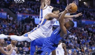 Oklahoma City Thunder guard Andre Roberson, center, blocks a shot by Dallas Mavericks guard Dennis Smith Jr. (1) in the second quarter of an NBA basketball game in Oklahoma City, Sunday, Nov. 12, 2017. (AP Photo/Sue Ogrocki)