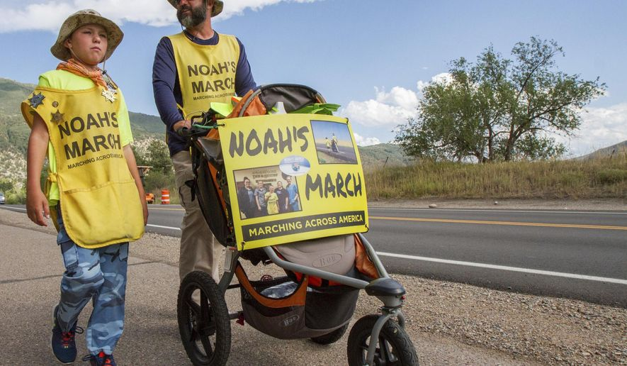 FILE - In this Aug. 9, 2017, file photo, Noah Barnes and his dad Robert make their way through Glenwood Springs, Colo., on Highway 6 as they travel across the country on foot. Noah Barnes is one determined 11-year-old. Thus far, the Fort Lauderdale, Fla., resident had racked up at least 3,200 miles when he reached Pendleton, en route to the finish line in Blaine, Wash. His journey started on Jan. 1 in Key West, Fla.,, and he expects to cover approximately 4,000 miles by Dec. 9. (Chelsea Self/Glenwood Springs Post Independent via AP, File)