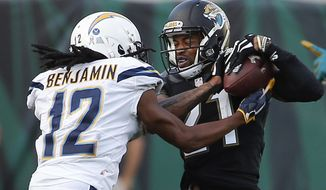 Jacksonville Jaguars cornerback A.J. Bouye , right, intercepts a pass intended for Los Angeles Chargers wide receiver Travis Benjamin (12) during the second half of an NFL football game, Sunday, Nov. 12, 2017, in Jacksonville, Fla. (AP Photo/Stephen B. Morton)